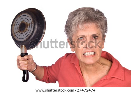 An angry mother threatens to swing her frying pan is a display of violent behavior. Image was shot against a lighted white background and is not a cutout. - stock photo