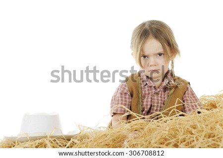 An angry preschool cowgirl sitting behind a pile of hay with her hat nearby.  On a white background with space for your text over her hat. - stock photo