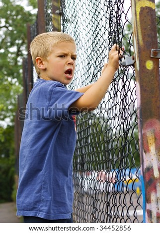 An angry young boy shouting through a chain link fence - stock photo
