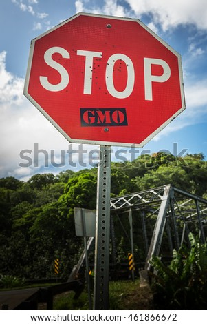 An anti-GMO sticker placed on a stop sign on the edge of the taro fields of Hanalei Valley on the island of Kauai, Hawaii