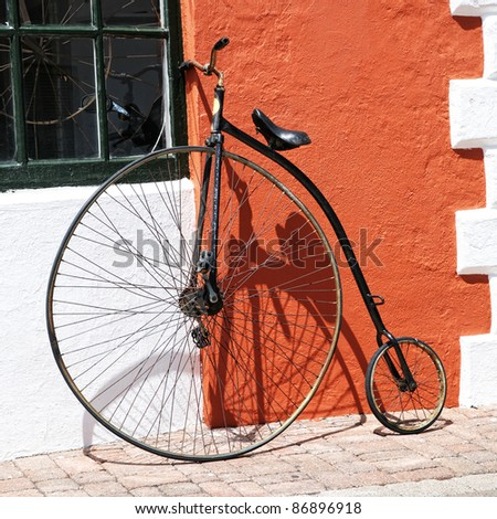 An antique bicycle leaning up against the stucco wall of a building.