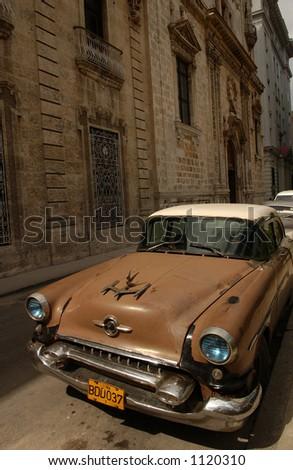 An antique car parked besides a building, Havana, Cuba - stock photo