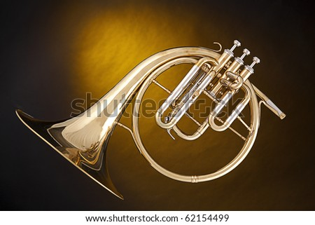 An antique French horn or peckhorn isolated against a spotlight yellow background with copy space. - stock photo