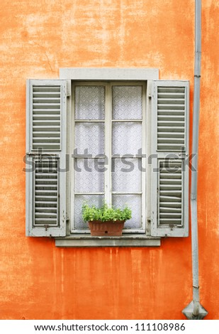An antique grungy closed window with opened shutter in a orange wall facade - stock photo