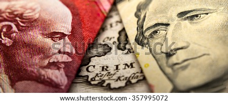 An antique map showing Crimea (Crim) in between a close-up of a Russian ruble banknote (figuring Lenin) and a 10 dollar banknote figuring Alexander Hamilton - stock photo