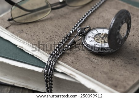 An antique pocket watch, glasses and books in close up - stock photo