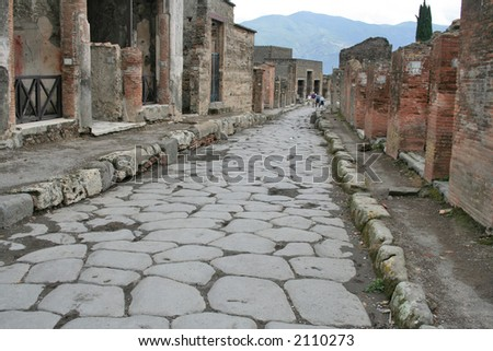 An antique roman stone street through ruins of Pompei,Italy. - stock photo