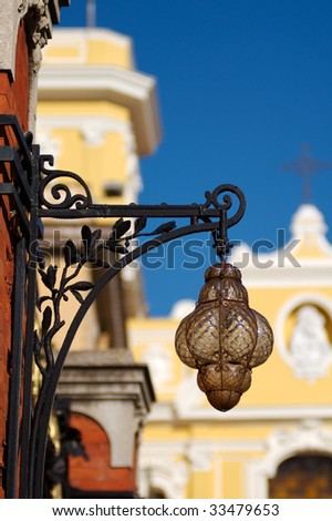 An antique street lamp, with the yellow cathedral in the background, Sorrento, Italy