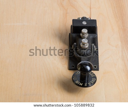 An antique telegraph key on a wooden desk - stock photo