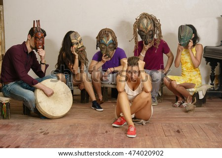 An anxious modern girl is surrounded by aborigines in ethnic masks