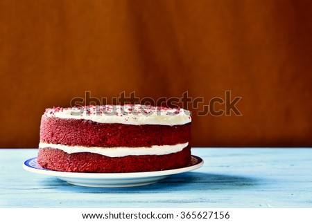 an appetizing red velvet cake on a rustic blue wooden table - stock photo