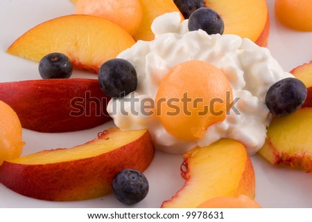 An appetizing snack or breakfast of fresh nectarine, cantaloupe, blueberries and cottage cheese. - stock photo