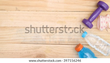 An apple, a measuring tape and dunbbell on wood  - stock photo