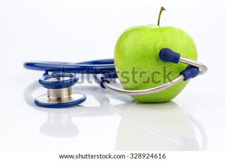 an apple and a stethoscope with a doctor. symbolic photo for healthy and vitamin-rich diet. - stock photo