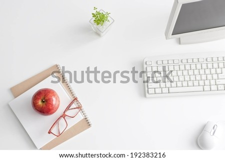 An apple and glasses on a notebook beside a plant and a computer. - stock photo