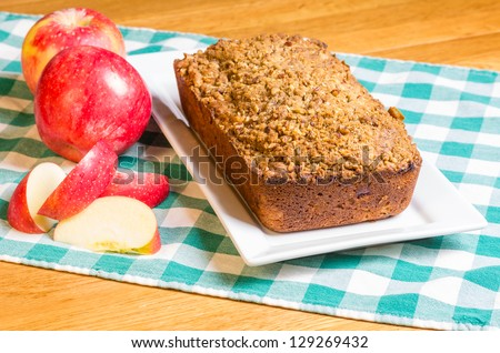 An apple cake on a white plate with red apples - stock photo