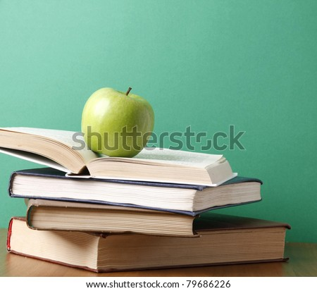 An apple on a pile of books - stock photo