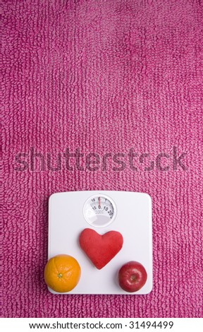 An apple, orange and a heart placed on scales, shot portrait. - stock photo