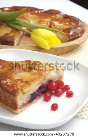 An Apple pie with a slice  and tulip