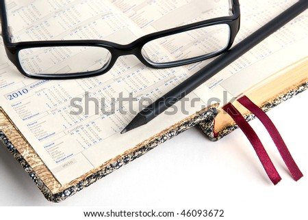 An appointment book with black glasses and a pencil