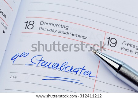 an appointment is entered on a calendar: tax consultants - stock photo