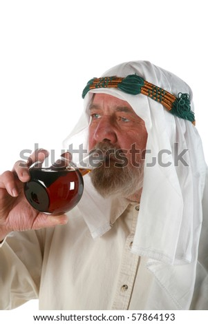 an Arabic chemical engineer holds and drinks a flask of crude oil isolated on white, representing american dependence on the oil industry - stock photo