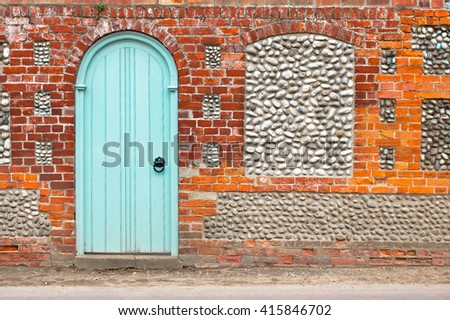 An arch door in a stone wall - stock photo