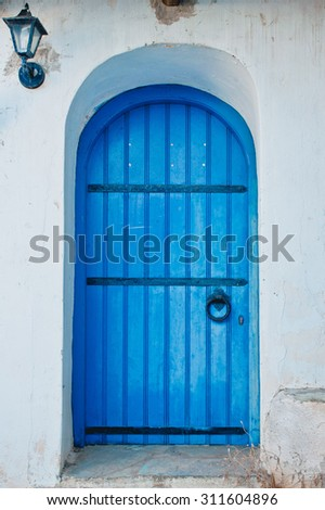 An arched blue wooden door in a greek house - stock photo