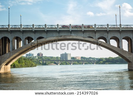 an arched concrete bridge framing skyscrapers and trees in the background with a river flowing underneath and a blue sky in the summer time - stock photo