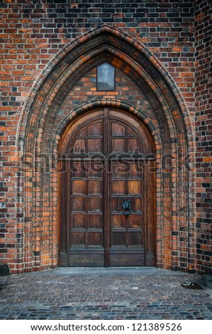 An arched doorway to a gothic style church. - stock photo