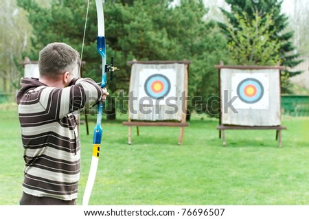 An archer with bow takes aim at a target during competition - stock photo
