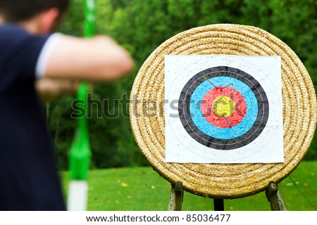 An archer with bow takes aim at target - stock photo