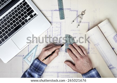 an architect making measurements on blueprints with ruler and using a computer - stock photo