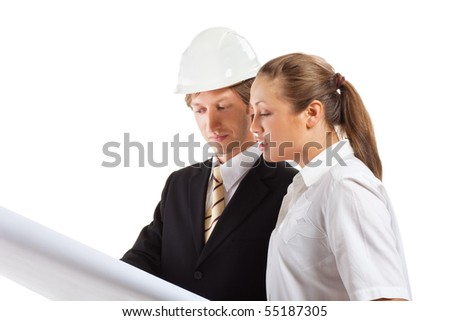 An architect wearing a hard hat and co-worker reviewing blueprints - stock photo
