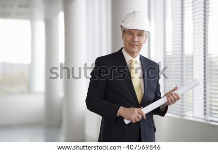 An architect wearing a hard hat holding plans - stock photo