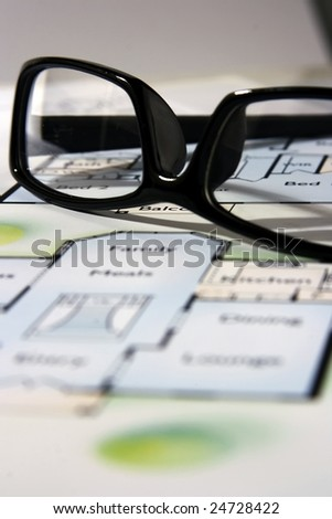 An architecture blueprint with black frame eyeglasses on top.