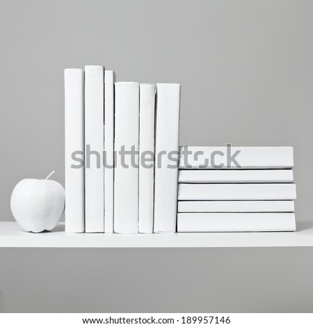 An arrangement of all white books sit on a white shelf with a white apple against a light grey background. - stock photo