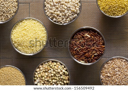 An arrangement of 8 different kinds of grain in small metal containers placed on a screen.   - stock photo