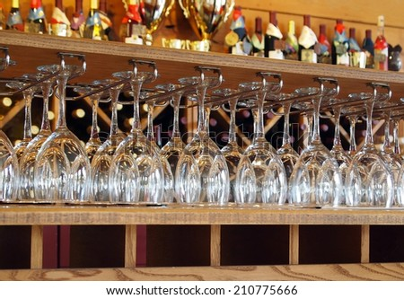 An arrangement of dozens of clean wine glasses hanging in racks in a tasting room at a winery. - stock photo