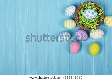An arrangement of Easter eggs and nest on a turquoise wooden background - stock photo