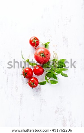 An arrangement of tomatoes and basil - stock photo