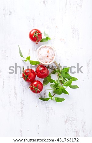 An arrangement of tomatoes, basil and himalayan salt - stock photo