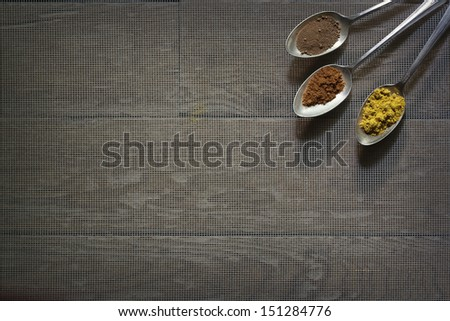 An arrangement of 3 vintage silver spoons with three different spices in them. - stock photo