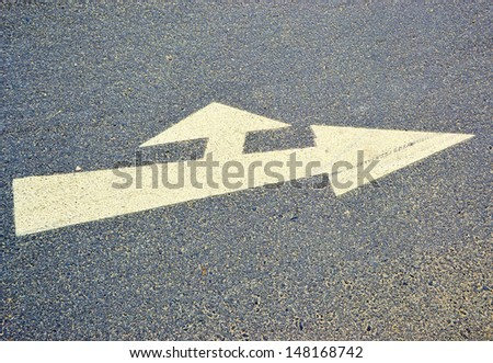 an arrow on the asphalt showing the direction of travel