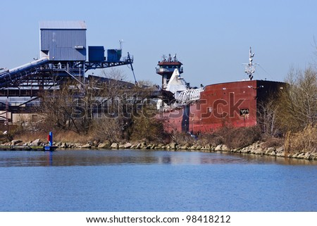 An articulated tugboat and barge is being loaded with taconite for delivery to a steel mill.  This bulk terminal is located in the Cleveland Harbor on Lake Erie - stock photo