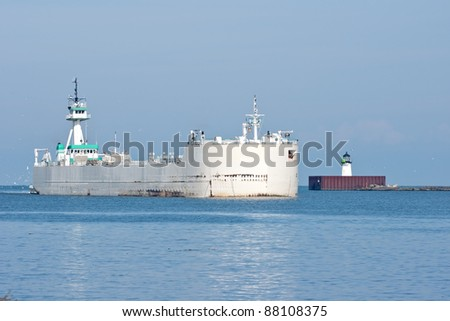 An articulated tugboat and cement barge enter the harbor at Cleveland, Ohio from Lake Erie headed for a large cement making facility on the banks of the Cuyahoga River - stock photo