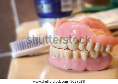An artificial denture of a senior in a glass of water with toothbrush and paste aside. Shallow depth of field and a bit of blur motion due to lightning technique. Sharp Focus on the teeth. - stock photo
