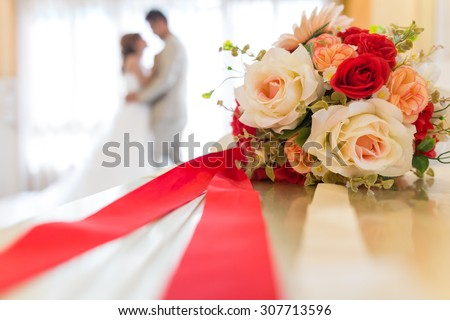 An artificial flower bouquet with blurred bride and groom background - stock photo