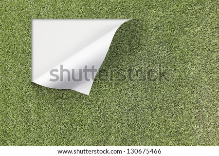 An artificial green grass turf surface peeling off at the edge with blank space for text. - stock photo