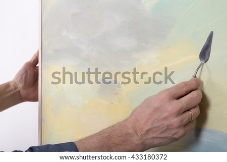 An artist painting with a palette knife in studio - stock photo